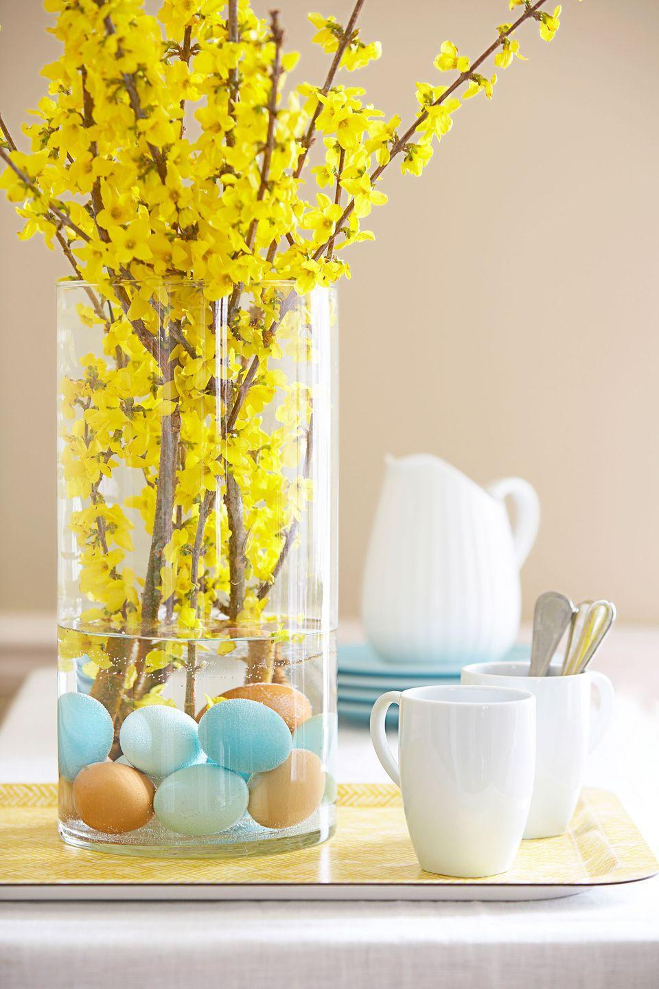 """<p>Anchor brilliant forsythia — and give a tongue-in-cheek nod to Easter — with subtly hued hard-cooked eggs. Carefully place a dozen brown, white, and dyed ones (rinse them well first) into a vase, add water, and insert branches.</p><p><a class=""""link rapid-noclick-resp"""" href=""""https://www.amazon.com/Hosley-Weddings-Aromatherapy-Projects-Lanterns/dp/B01N8WU35P?tag=syn-yahoo-20&ascsubtag=%5Bartid%7C10055.g.2217%5Bsrc%7Cyahoo-us"""" rel=""""nofollow noopener"""" target=""""_blank"""" data-ylk=""""slk:BUY VASE"""">BUY VASE</a></p>"""