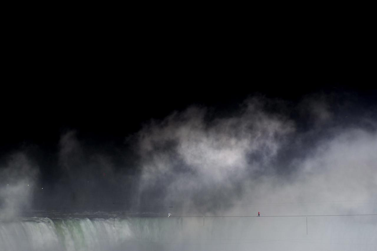 Nik Wallenda walks a tightrope over Niagara Falls as seen from Niagara Falls, Ontario, on Friday, June 15, 2012. Wallenda has finished his attempt to become the first person to walk on a tightrope 1,800 feet across the mist-fogged brink of roaring Niagara Falls. The seventh-generation member of the famed Flying Wallendas had long dreamed of pulling off the stunt, never before attempted. (AP Photo/The Canadian Press, Nathan Denette)