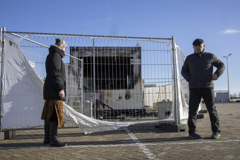A person looks at a torched coronavirus testing facility in the Dutch fishing village of Urk, Sunday, Jan. 24, 2021, after it was set ablaze Saturday night by rioting youths protesting on the first night of a nation-wide curfew. (AP Photo/Peter Dejong)