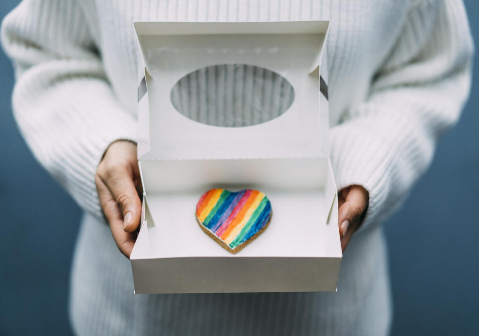 Woman holding box with heart shape cookie in lgbt colors