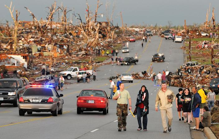 FILE - In this May 22, 2011, file photo residents walk in the street after a massive tornado hit Joplin, Mo. The National Weather Service is kicking off an experiment starting April 2, 2012 with a new kind of tornado warning that's aimed to scare people into seeking shelter.(AP Photo/Mike Gullett, File)