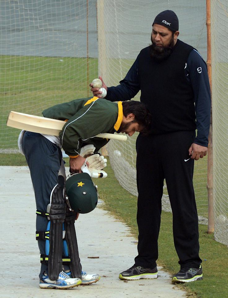 Former Pakistani cricket captain and team batting coach Inzamam-ul Haq (R) and cricketer Shahid Afridi (L) interact during a team practice session at the Gaddafi stadium in Lahore on December 15, 2012. Pakistan starts a week-long training camp for its landmark limited overs series against India with former captain Inzamam-ul Haq and a psychologist drafted in, an official said.  AFP PHOTO/Arif ALI