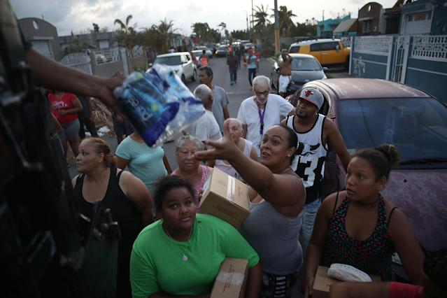 <p>Hurricane survivors receive food and water being given out by volunteers and municipal police as they deal with the aftermath of Hurricane Maria on Sept. 28, 2017 in Toa Baja, Puerto Rico. (Photo: Joe Raedle/Getty Images) </p>