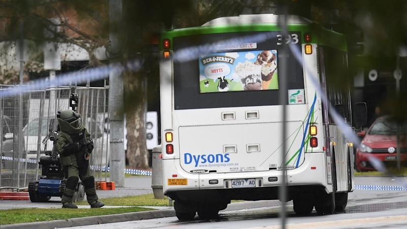Bomb squad robots are examining a bus parked near a suburban Melbourne police station.