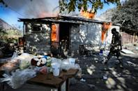 A man walks past as a house burns in the village of Charektar on Saturday