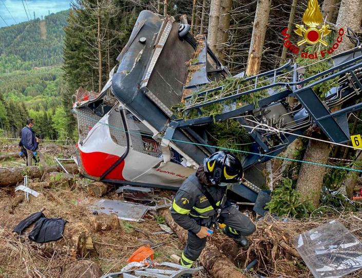 Rescuers work by the wreckage of a cable car after it collapsed near the summit of the Stresa-Mottarone line in the Piedmont region, northern Italy, Sunday, May 23, 2021. A cable car taking visitors to a mountaintop view of some of northern Italy's most picturesque lakes plummeted to the ground Sunday and then tumbled down the slope, killing at least 13 people and sending two children to the hospital, authorities said. (Italian Vigili del Fuoco Firefighters via AP)