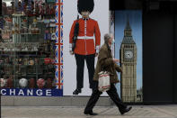 A person wearing a face mask walks past a temporarily closed souvenir store on Oxford Street, during England's second coronavirus lockdown, in London, Monday, Nov. 23, 2020. British Prime Minister Boris Johnson has announced plans for strict regional measures to combat COVID-19 after England's second lockdown ends Dec. 2, sparking a rebellion by members of his own party who say the move may do more harm than good. (AP Photo/Matt Dunham)