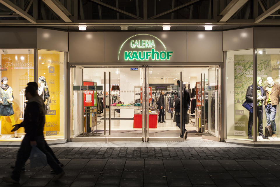 Wiesbaden, Germany - February 15, 2014: Illuminated entrance of Galeria Kaufhof in the city center of Wiesbaden. Galeria Kaufhof is a department store chain in Germany. It belongs to Metro AG, which is based in Duesseldorf, Germany. Some shoppers inside the store