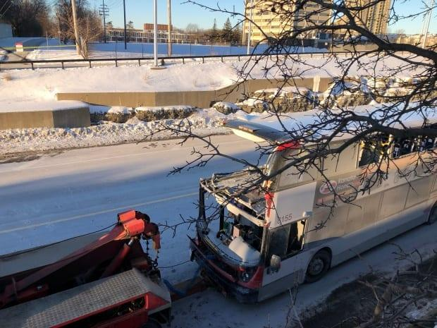 A tow truck pulls away a damaged OC Transpo bus from Westboro station on Jan. 12, 2019. The double-decker bus struck the shelter the day before.