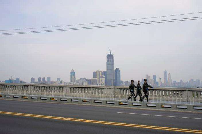 Paramilitary officers wearing face masks walk on a bridge in Wuhan