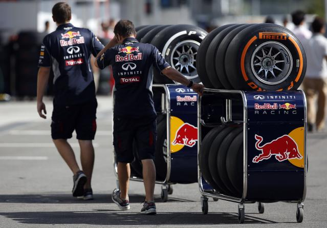 Red Bull Formula One team members move Pirelli tires near the pits at the Suzuka circuit in Suzuka October 10, 2013, ahead of Sunday's Japanese F1 Grand Prix. REUTERS/Issei Kato (JAPAN - Tags: SPORT MOTORSPORT F1)