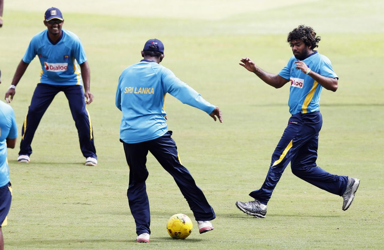 Sri Lanka's Lasith Malinga (R) runs for the ball next to Ajantha Mendis (C) during a practice session ahead of their first One Day International cricket match against South Africa in Colombo July 5, 2014. Sri Lanka's and South Africa's teams will play three One-Day International (ODI) matches and two test matches starting from July 6. REUTERS/Dinuka Liyanawatte (SRI LANKA - Tags: SPORT CRICKET)