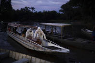 """SOS Funeral workers transport by boat a coffin carrying the body of an 86-year-old woman who lived by the Negro River and is suspected to have died of COVID-19, near Manaus, Brazil, May 14, 2020. Associated Press photographer Felipe Dana says this of shooting the photo: """"I'll never forget the scene of the funeral service workers wearing full hazmat suits, navigating along the Negro River as the sun disappeared in the horizon. It was the moment I realized how the virus had spread everywhere."""" (AP Photo/Felipe Dana)"""