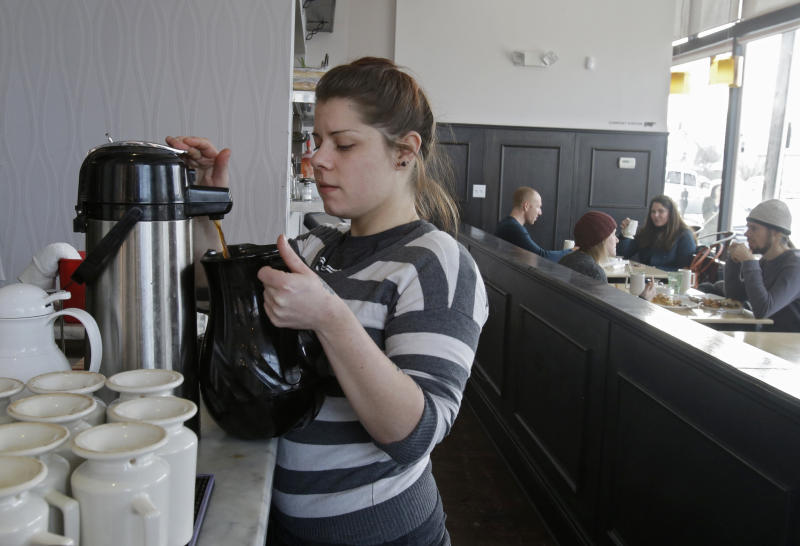 In this Tuesday, Jan. 28, 2014 photo, server Coleen Pratt fills a carafe with hot coffee at Bonbon Pastry and Cafe in Cleveland. Single-digit temperatures across the U.S. and record snowfalls in the Midwest since the beginning of January have put the freeze on businesses that rely on walk-ins and appointments. At the cafe in the city's Market Square district, the past weekend was especially slow with whiteout conditions making going outside unappealing for customers. (AP Photo)