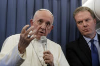 Pope Francis, flanked by Vatican spokesperson Greg Burke, listens to a journalist's question during a press conference aboard of the flight to Rome at the end of his two-day visit to Ireland, Sunday, Aug. 26, 2018. (AP Photo/Gregorio Borgia, Pool)