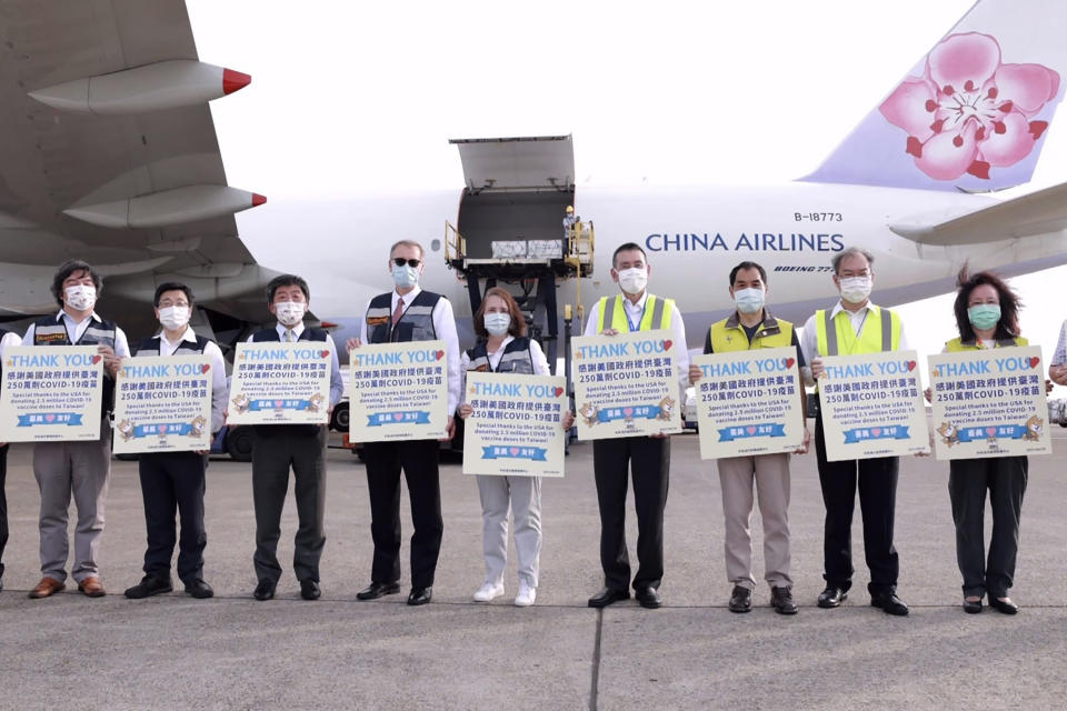 In this photo released by the Taiwan Centers for Disease Control, Taiwan's Health Minister Chen Shih-chung, third from left, and Brent Christensen, the top U.S. official in Taiwan, fourth from left, hold up thank you cards as they welcome a China Airlines cargo plane carrying COVID-19 vaccines from Memphis that arrived at the airport outside Taipei in Taiwan on Sunday, June 20, 2021. The U.S. sent 2.5 million doses of the Moderna COVID-19 vaccine to Taiwan on Sunday, tripling an earlier pledge in a donation with both public health and geopolitical meaning. (Taiwan Centers for Disease Control via AP)