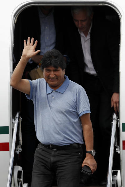 Former Bolivian President Evo Morales waves upon arrival in Mexico City, Tuesday, Nov. 12, 2019. Mexico granted asylum to Morales, who resigned on Nov. 10 under mounting pressure from the military and the public after his re-election victory triggered weeks of fraud allegations and deadly protests. (AP Photo/Eduardo Verdugo)