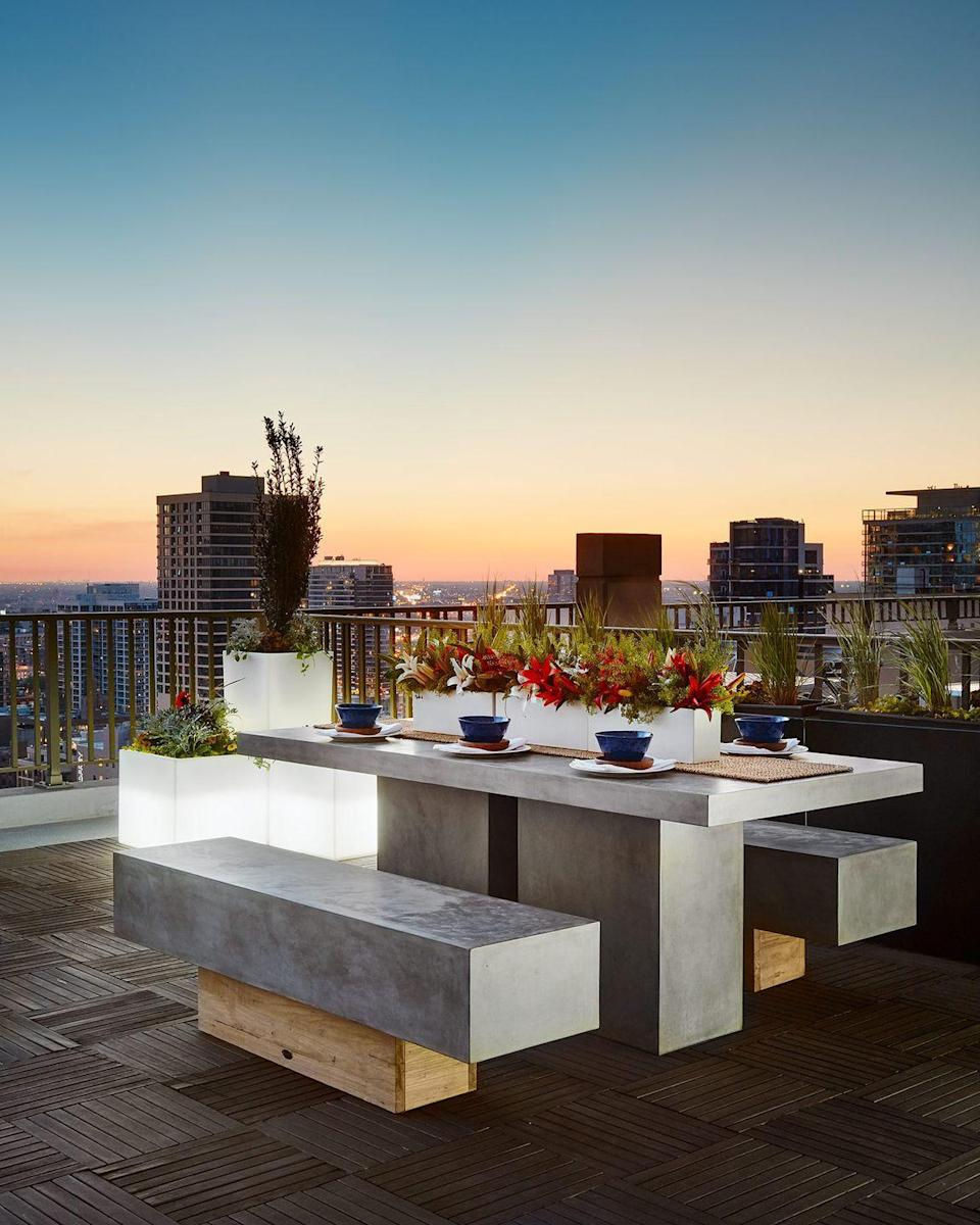 "<p>A Gold Coast private rooftop deck conjures modern picnic vibes, with a stone-and-wood dining table that's backed by sprawling city views.</p><p><em>Design by <a href=""https://deringhall.com/interior-designers/inspired-interiors"" rel=""nofollow noopener"" target=""_blank"" data-ylk=""slk:Inspired Interiors"" class=""link rapid-noclick-resp"">Inspired Interiors</a></em></p>"