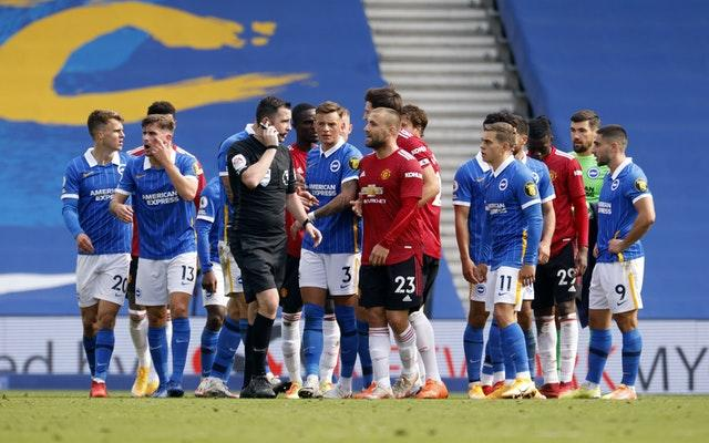Chris Kavanagh is surrounded by players in the final moments of the game as he checks a VAR penalty decision which resulted in Manchester United's Miguel Bruno Fernandes scoring the winning goal during the Premier League match at the AMEX Stadium