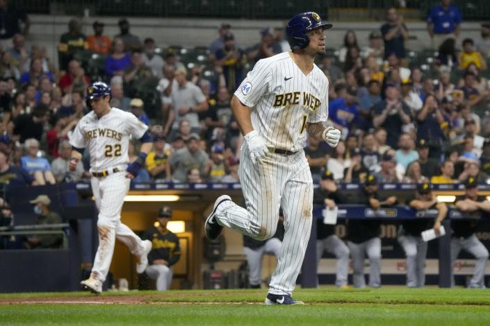 Milwaukee Brewers' Jace Peterson heads to first as Christian Yelich heads home after a walk with bases loaded during the seventh inning of a baseball game against the Pittsburgh Pirates Friday, June 11, 2021, in Milwaukee. (AP Photo/Morry Gash)