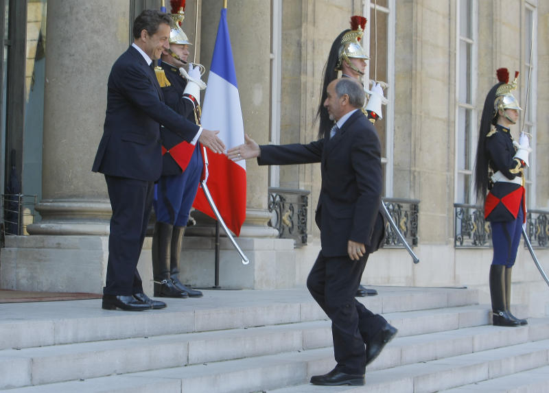France's President Nicolas Sarkozy, left, welcomes Libyan National Transitional Council's  Mustapha Abdeljalil at the Elysee Palace in Paris, France, Wednesday, April 20, 2011.  France's government said Wednesday, it will send a small number of military liaison officers to Libya to work with opposition forces, but no ground troops.(AP Photo/Jacques Brinon)