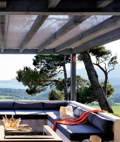 Shaded by a pergola topped with all-weather Batyline fabric, the ipê terrace at a summer home in the South of France was designed by architect Ann Guillec with decorator Florence Watine. The concrete banquette's low back maximizes the view of the Saint-Tropez coastline. The cocktail table is made of reclaimed wood, and the armchair is teak. (Photo: Nicolas Tosi