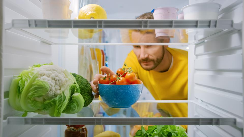 Inside Kitchen Fridge: Handsome Man Takes Cherry Tomatoes from Opened Fridge. Man Preparing Healthy Meal. Point of View POV Shot from Refrigerator full of Healthy Food