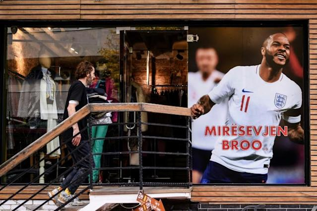 """a clothing store in Pristina put up a giant banner with a picture of Raheem Sterling, the Manchester City star, with an inscription """"Miresevjen broo (Welcome bro)"""" (AFP Photo/Armend NIMANI)"""