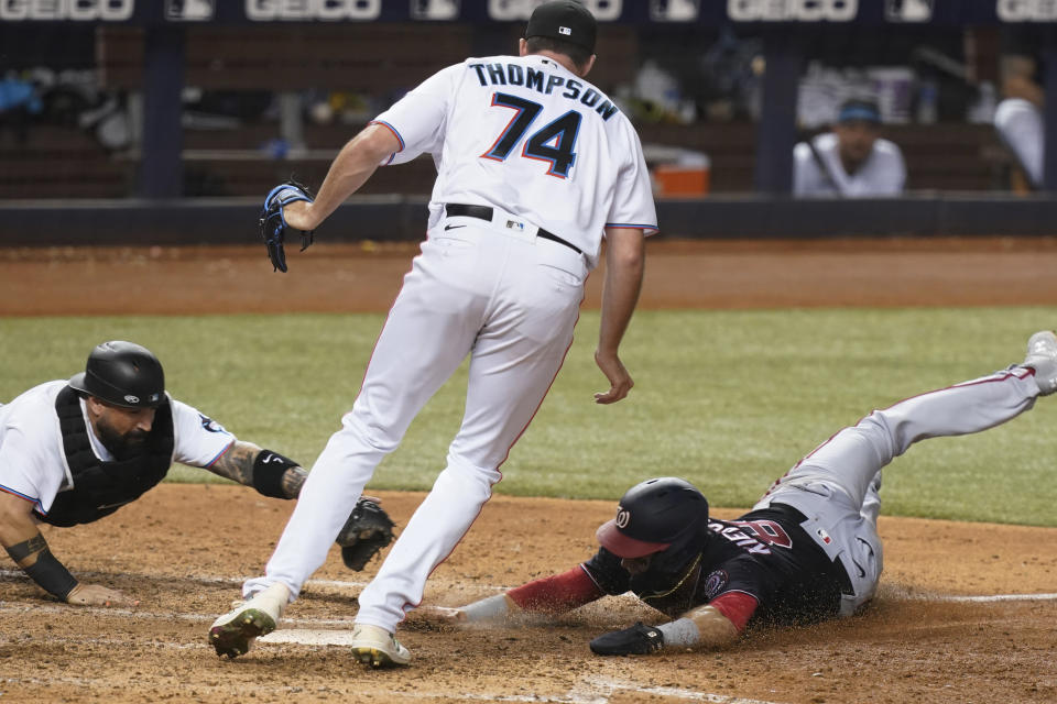 Miami Marlins' catcher Sandy Leon, left, stretches to tag Washington Nationals' Carter Kieboom (8) who was trying to score on a wild pitch while Marlins relief pitcher Zach Thompson (74) stands between them during the seventh inning of a baseball game, Monday, Sept. 20, 2021, in Miami. (AP Photo/Marta Lavandier)