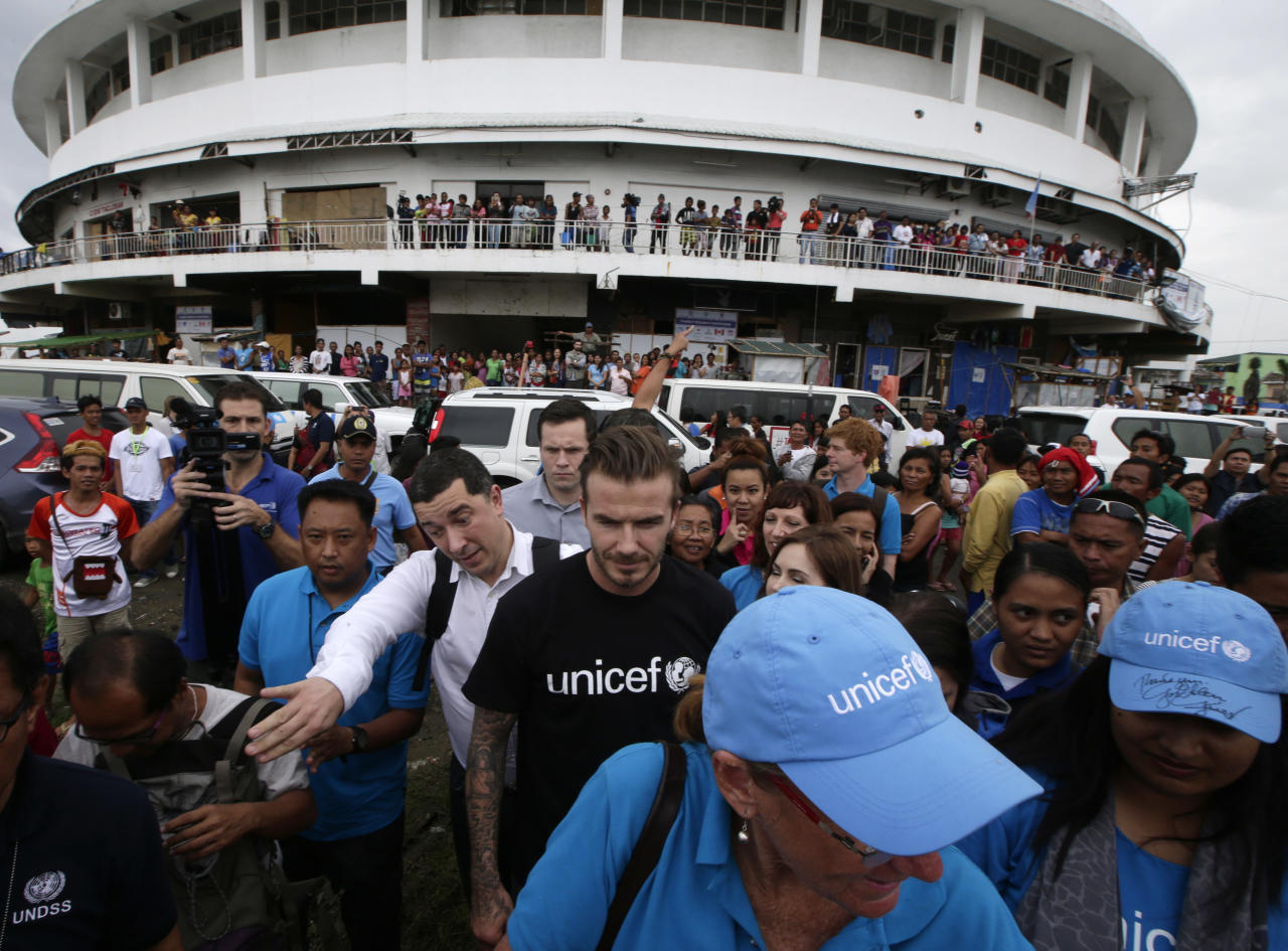 Former England soccer team captain David Beckham arrives to interact with typhoon survivors during his visit nearly a hundred days after typhoon Haiyan (local name Yolanda) devastated Tacloban city and other provinces in central Philippines Thursday, Feb. 13, 2014. Beckham and his wife were one of several international celebrities to raise funds for typhoon victims. (AP Photo/Bullit Marquez)