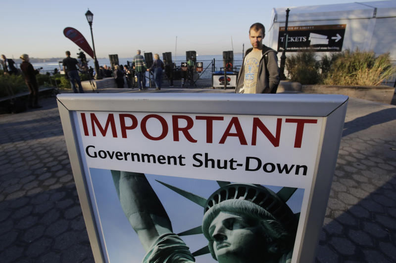 A park ranger, who declined to give his name, reads a sign announcing the closing of the Statue of Liberty, Tuesday, Oct. 1, 2013, in New York. Congress plunged the nation into a partial government shutdown Tuesday as a long-running dispute over President Barack Obama's health care law forced about 800,000 federal workers off the job, suspending all but essential services. (AP Photo/Mark Lennihan)