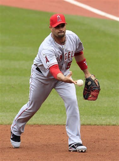 Los Angeles Angels first baseman Albert Pujols tosses the ball to starting pitcher Dan Haren to get Cleveland Indians' Casey Kotchman out at first base in the third inning in a baseball game, Saturday, April 28, 2012, in Cleveland. (AP Photo/Tony Dejak)