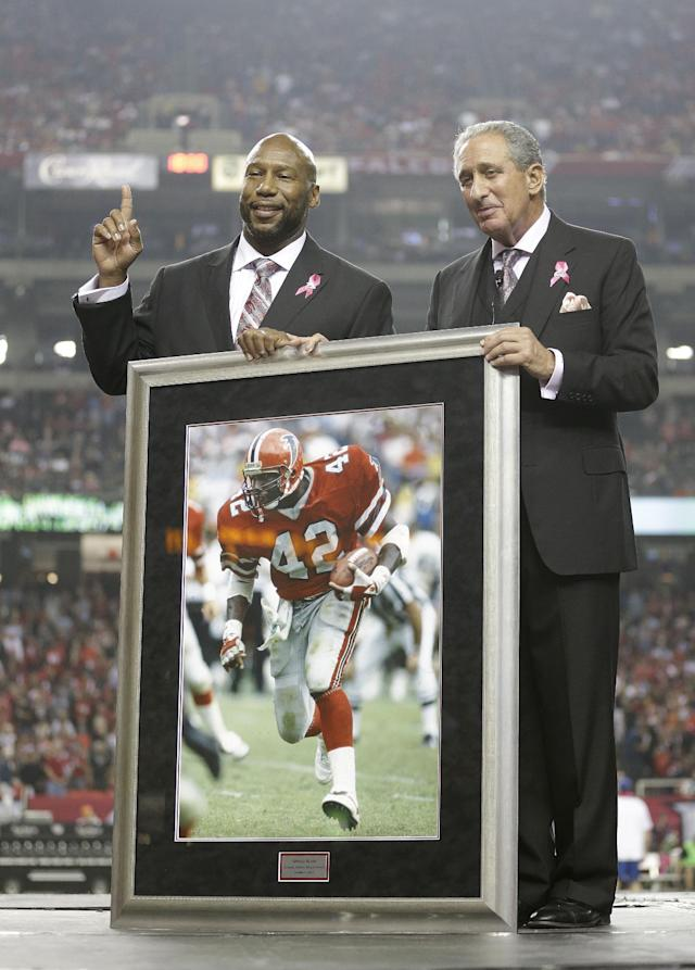 Former Atlanta Falcons running back Gerald Riggs is honored by Atlanta Falcons owner Arthur Blank into the ring of honor during halftime of an NFL football game against the New York Jets, Monday, Oct. 7, 2013, in Atlanta. Riggs played for the Atlanta Falcons from 1982-1988. (AP Photo/John Bazemore)