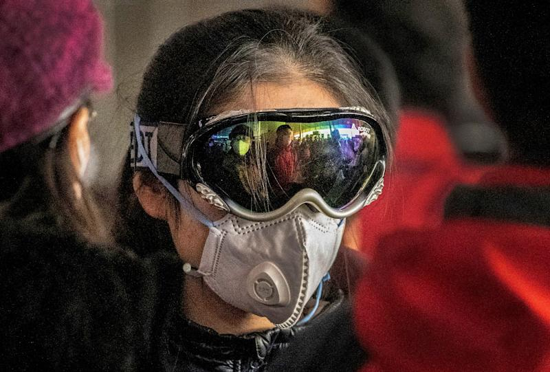 CHINA: A woman wears ski goggles and a protective mask as she checks in to a flight at Beijing Capital Airport.