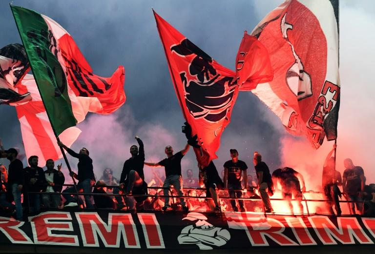 AC Milan fans wave flags during the city derby against Inter Milan in the San Siro stadium