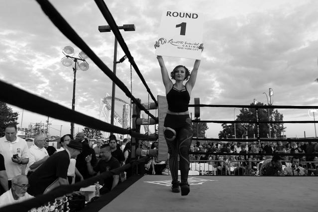 <p>Female police officers served as round card girls, strutting around the ring for the Brooklyn Smoker in the parking lot of Gargiulo's Italian restaurant in Coney Island, Brooklyn, on Aug. 24, 2017. (Photo: Gordon Donovan/Yahoo News) </p>