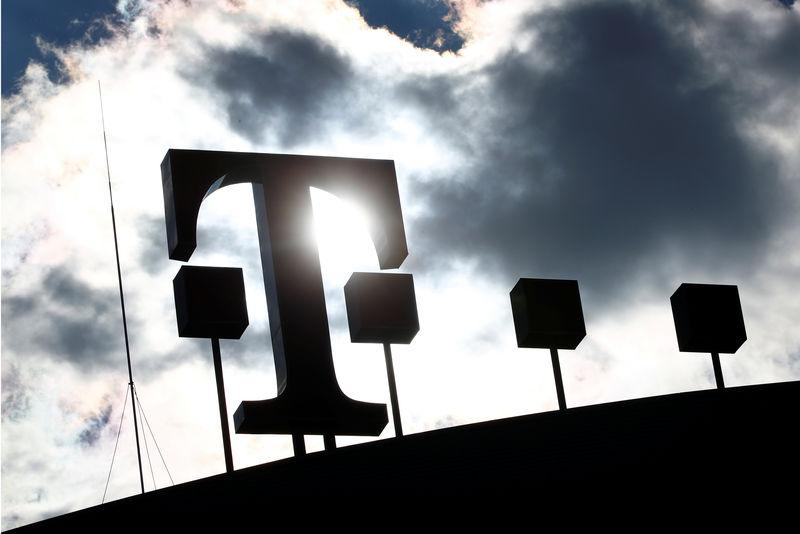 FILE PHOTO: Logo of Deutsche Telekom AG is silhouetted atop of the headquarters of German telecommunications giant in Bonn