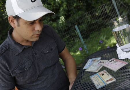 Alain Izquierdo, a Havana butcher and one of 15 survivors of the 32 Cuban migrants who were left adrift in Caribbean waters during their voyage, looks at identification documents of his late friend Rafael Baratuti O'Farrill, who died during the journey, while speaking with Reuters at his uncle's home in Port St. Lucie, Florida, October 3, 2014. REUTERS/Rickey Rogers