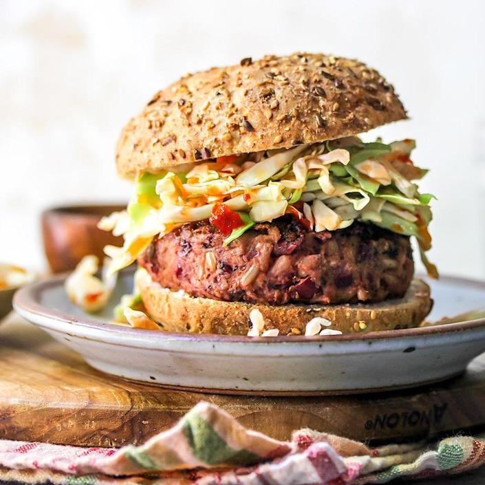 """<p>If you've been curious about those store-bought veggie burgers that """"bleed,"""" you should try this homemade veggie burger recipe made with kidney beans, walnuts and beets. A little chili powder in the mixture gives them a hint of spiciness, which works nicely with the sweet chili slaw.</p>"""