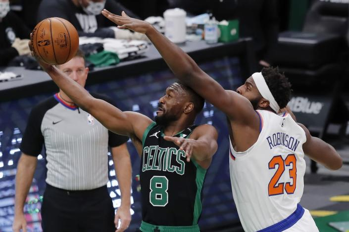 Boston Celtics' Kemba Walker (8) shoots against New York Knicks' Mitchell Robinson (23) during the first half of an NBA basketball game, Sunday, Jan. 17, 2021, in Boston. (AP Photo/Michael Dwyer)