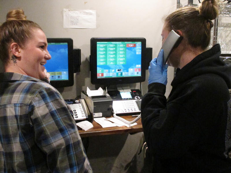 In this March 24, 2020 photo, Kirsten Phillips, left, and Sylvia Pappa, right, take telephone orders at Federico's Pizza in Belmar N.J. The owners of the business took out a $50,000 line of credit to ensure that their employees can stay on the payroll for at least two months during the virus outbreak. That prompted an outpouring of donations from customers wanting to send pizzas to hospital workers and first responders. (AP Photo/Wayne Parry)