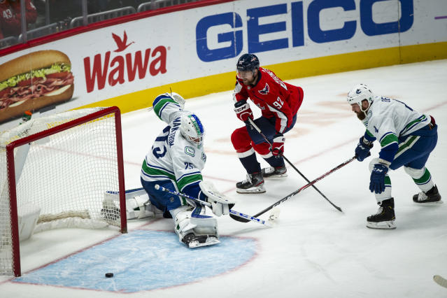 Washington Capitals center Evgeny Kuznetsov (92), from Russia, shoots the puck as Vancouver Canucks goaltender Jacob Markstrom (25) from Sweden, and defenseman Jordie Benn (4), from Canada, defend during the first period of an NHL hockey game, Saturday, Nov. 23, 2019, in Washington. (AP Photo/Al Drago)