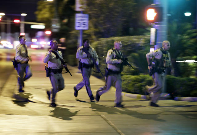 <p>Police run to cover at the scene of a shooting near the Mandalay Bay resort and casino on the Las Vegas Strip, Oct. 1, 2017, in Las Vegas. Multiple victims were being transported to hospitals after a shooting late Sunday at a music festival on the Las Vegas Strip. (Photo: John Locher/AP) </p>