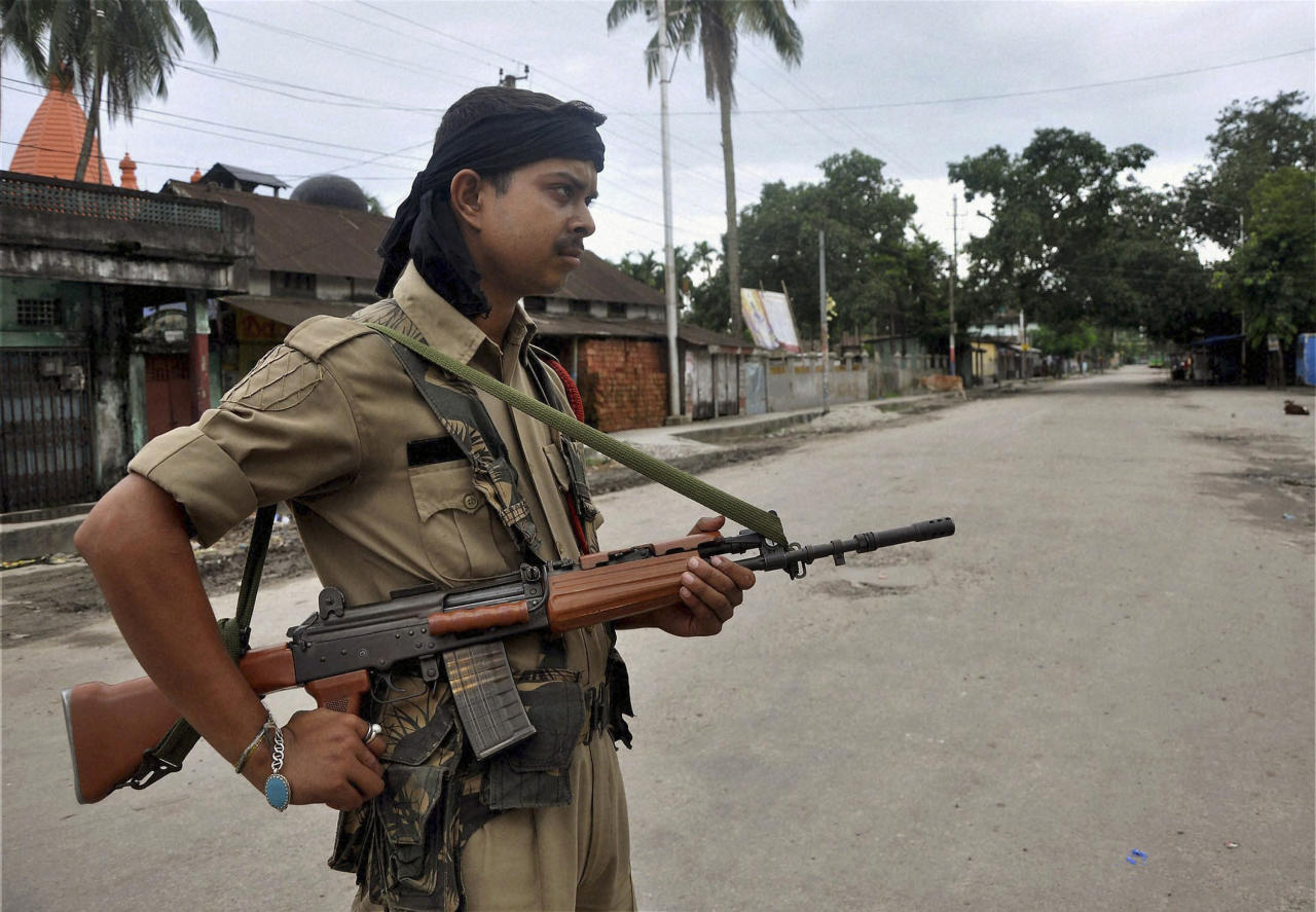 ADD STATE - An Indian armed security man stands guard in a riot-hit locality in Kokrajhar, India, Tuesday, July 24, 2012. Government troops sent to quell communal clashes over land rights in the northeast Indian state of Assam were under orders Tuesday to shoot suspected rioters on sight after some 21 people were killed in machete attacks and dozens of homes were burned to the ground. (AP Photo)