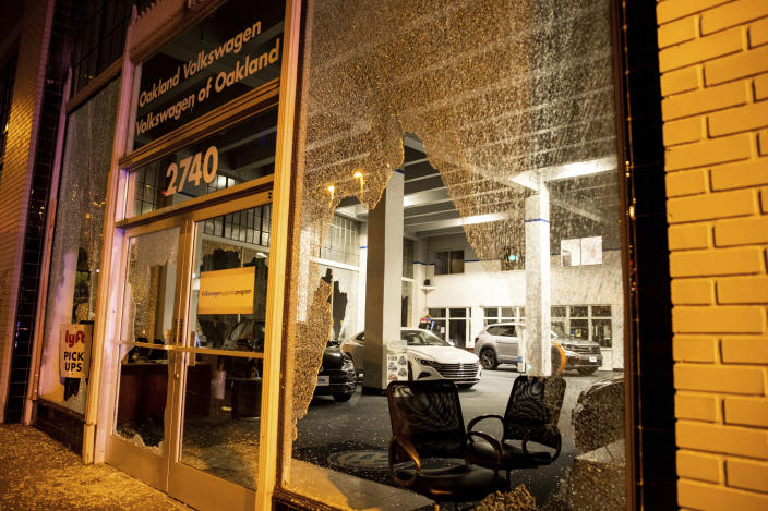 Windows of a Volkswagen dealership are shattered during a protest against police brutality in Oakland, Calif., on Friday, April 16, 2021. (AP Photo/Ethan Swope)