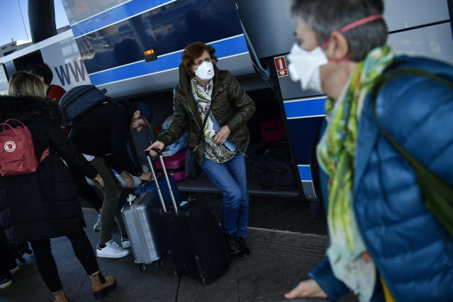 Passengers wearing a masks arrive at the bus station, in Vitoria, northern Spain, Saturday March 14, 2020. Spain's prime minister has announced a two-week state of emergency from Saturday in a bid to contain the new coronavirus outbreak. For most people, the new COVID-19 coronavirus causes only mild or moderate symptoms, such as fever and cough, but for some, especially older adults and people with existing health problems, it can cause more severe illness, including pneumonia. (AP Photo/Alvaro Barrientos)