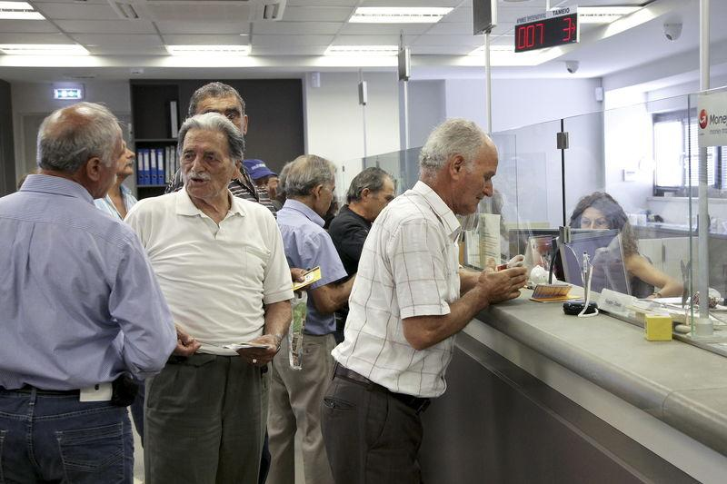 People make transactions at a counter inside a Piraeus Bank branch at the city of Iraklio in the island of Crete