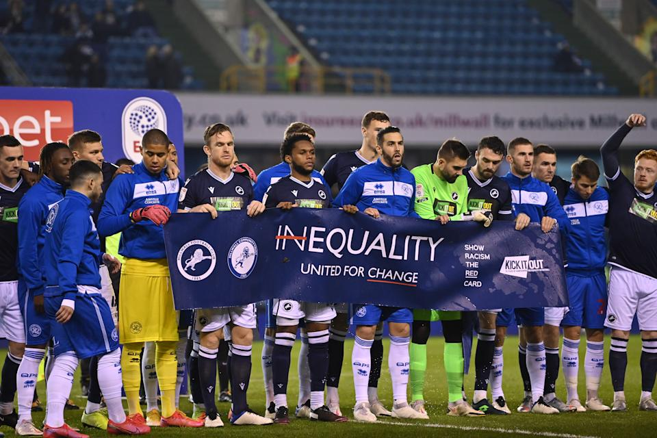 Millwall and Queens Park Rangers players held up a banner promoting equality before their game Tuesday in response to Saturday's Millwall fans booing kneeling. (Photo by Justin Setterfield/Getty Images)