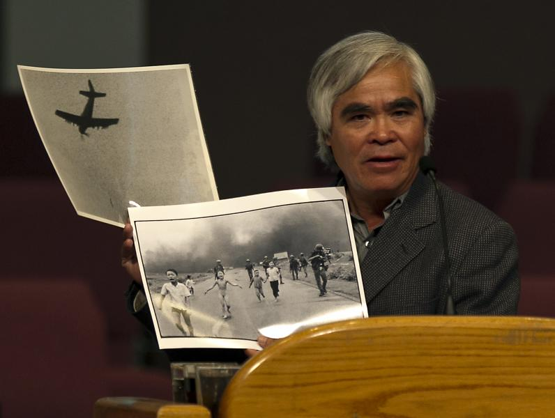 """FILE- In this Sunday, June 3, 2012, file photo, Associated Press staff photographer Nick Ut shows his famous photograph of the """"Napalm Girl"""" at Liberty Baptist Church in Newport Beach, Calif. It only took a second for Ut to snap the iconic black-and-white image of Phan Thi Kim Phuc after a napalm attack in 1972, but it communicated the horrors of the Vietnam War in a way words could never describe, helping to end one of America's darkest eras. (AP Photo/Damian Dovarganes, File)"""