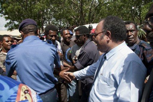 Papua New Guinea police hold back protesters as Peter O'Neill greets (R) supporters in 2011